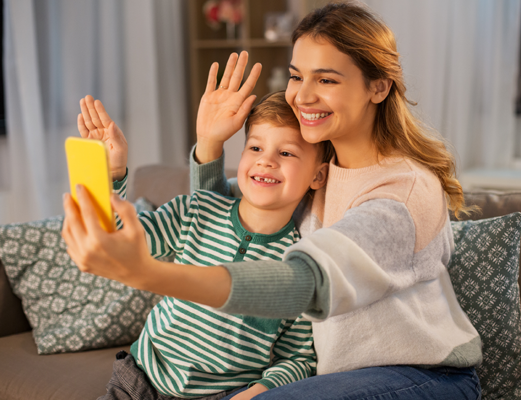 Mother and son waving at phone
