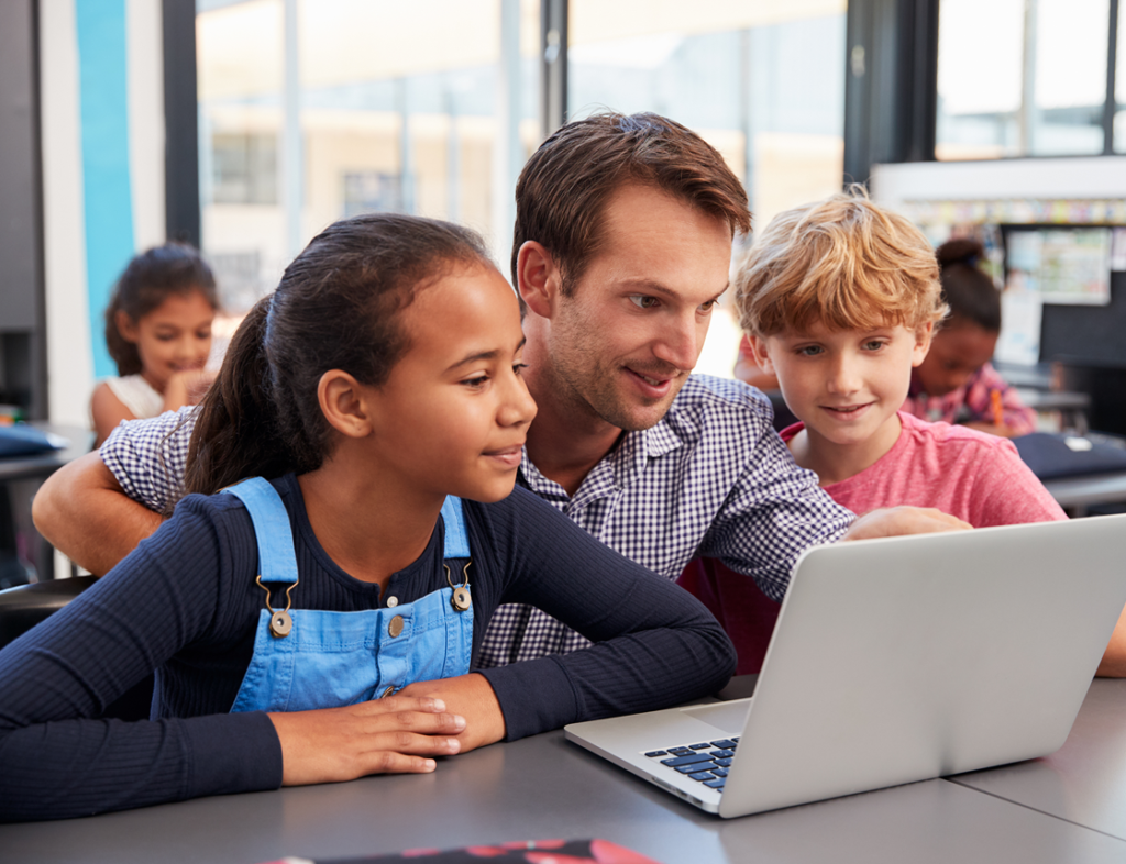 Kids looking at a computer with adult
