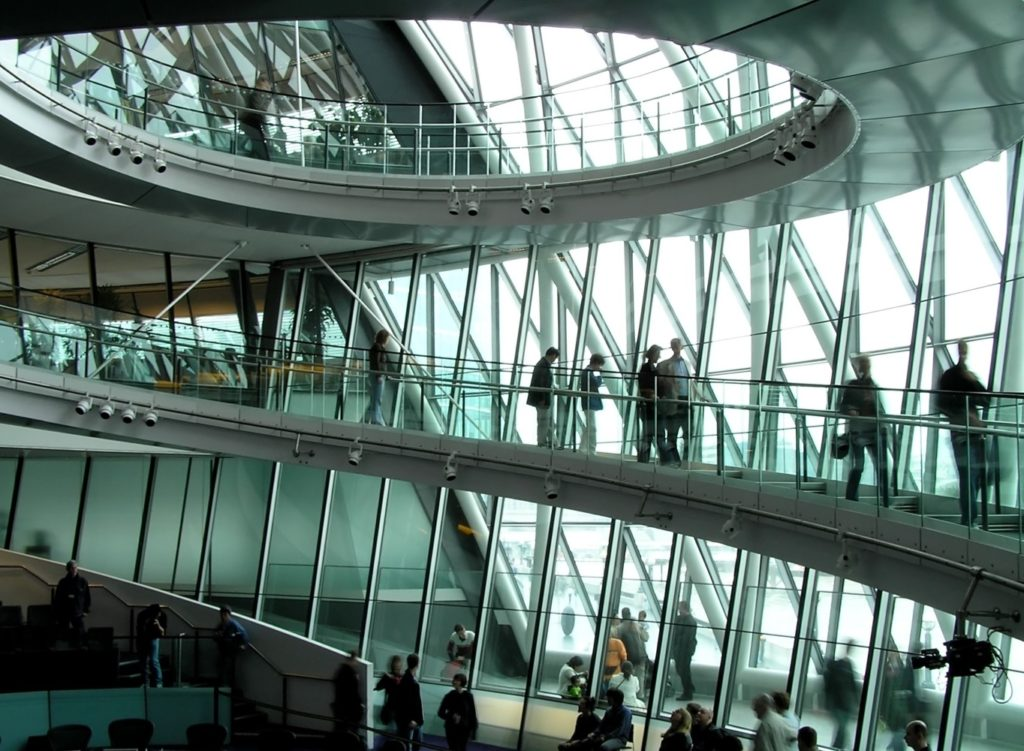 People walking up a ramp inside a glass building