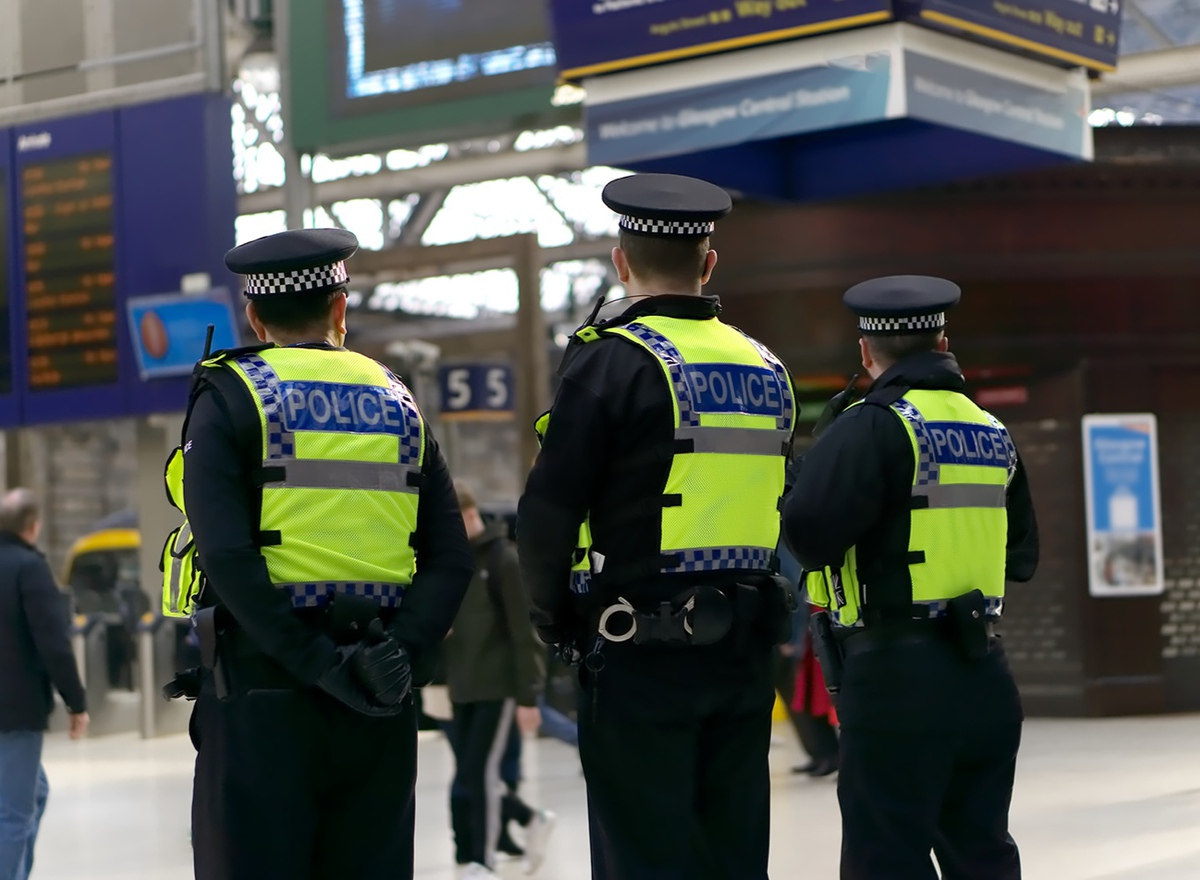 Policemen standing in a train station