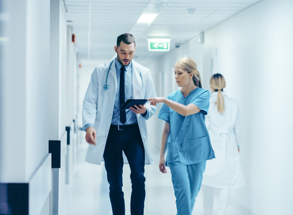 Doctor and nurse walking together looking at an ipad