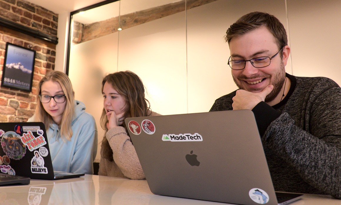 Three people working on laptops at a table